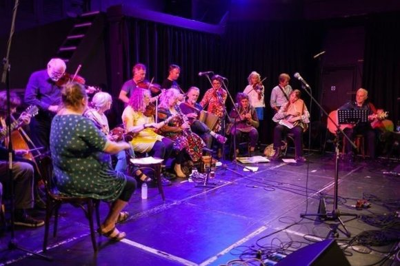 Several musicians playing Cornish music on stage including fiddles, clarinet, mandolin and bouzouki, guitar, melodeons, recorder, side drum, autoharp and bass viol.
