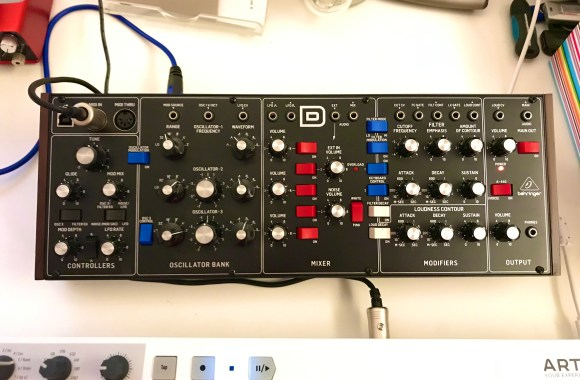 Photograph of a Beringer Model D synthesiser, black with blue and red switches, silver topped black knobs and wires coming out.