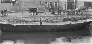 Pilchard seine boat on the River Kenwyn at Back Quay in Truro, with Samuel Brokenshire carriage factory in the background. A number of carts and carriages are parked on the quay, with a number of onlookers who are possibly workers from the factory. The coach builder, Samuel Brokenshire (also a shoeing smith) is recorded in Kelly's Directory, 1889, at Back Quay, Royal Hotel Yard, Truro. The main Fisheries Exhibition site was a field at the top of Lemon Street and the exhibition ran from 25th July 1893 for a month. Number 11 in a series of glass lantern slides recording the Fisheries Exhibition.