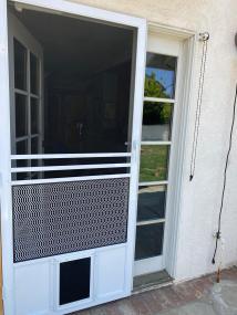Colonial door with small pet door installed in white.