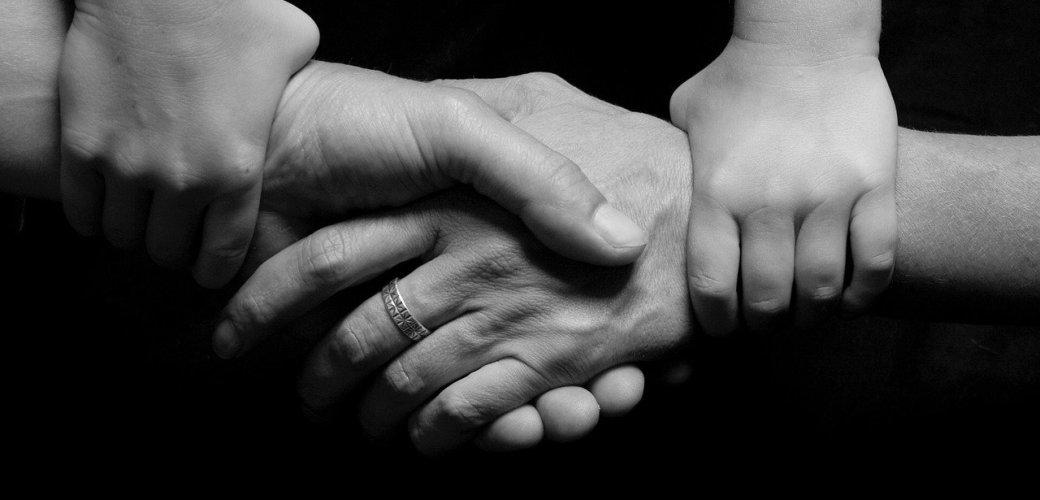 hand van man vrouw en kind die elkaar vasthouden