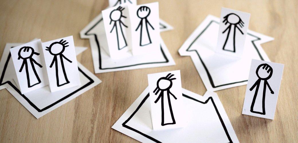 simpel getekende mensen op papier staant in simpel getekende huizen van elkaar vandaan