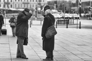 two older gentlemen raising their hats to each other on a square