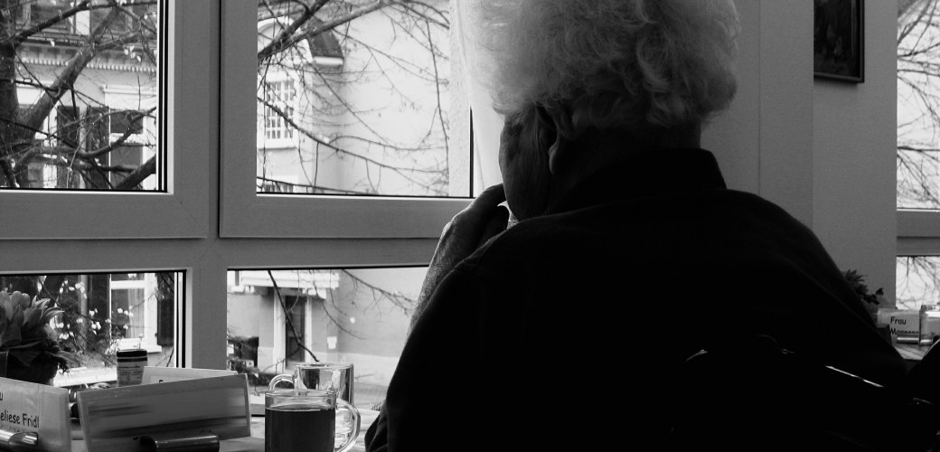 elderly woman staring out of a window