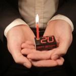 Happy Birthday Box mit brennender Kerze in den Händen