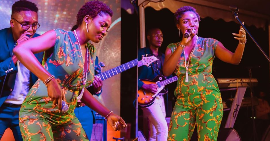 Simi performs on stage with a very visible baby bump