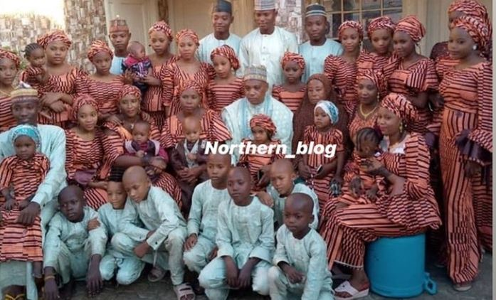 Hausa man poses with his four wives and 33 children