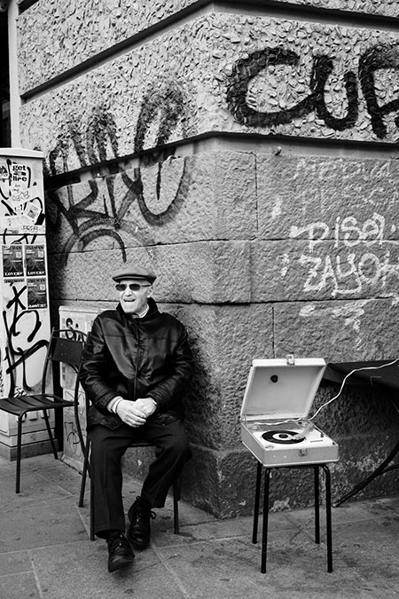 Anziano seduto all'angolo della strada che ascolta il giradischi
