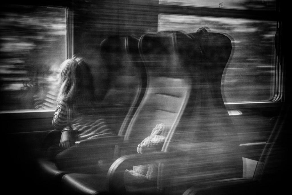 Bambina con peluche che guarda fuori dal finestrino di un treno in movimento