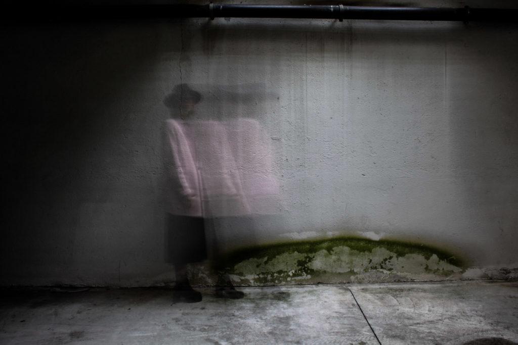 Immagine di una donna con giacca rosa che cammina