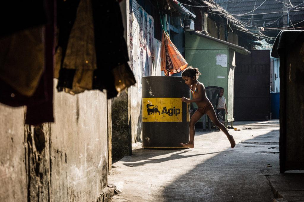 Bambina corre tra le baracche in una favelas