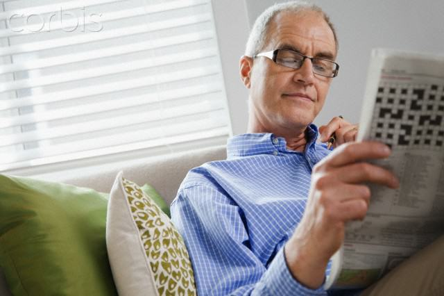 Smiling middle-aged man reading newspaper on sofa --- Image by © Kate Kunz/Corbis