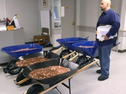 Nick Stafford waits for his number to be called as he stands beside five wheelbarrows full of change, mostly pennies, at the DMV in Lebanon, Virginia. Stafford was paying the sales tax on two cars that he was titling.