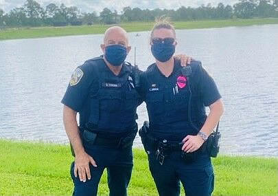 Officers Corona and Drug rescue a man from a lake in Port St. Lucie. (Port St. Lucie Police)