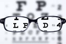 Icon with glasses that magnify letters on an eye exam chart
