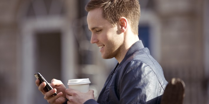 person holding phone with coffee