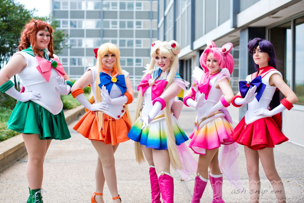 5 cosplayers dressed as Sailor Jupiter, Sailor Venus, Super Sailor Moon, Super Sailor Chibi Moon, and Sailor Mars, posed in a line.