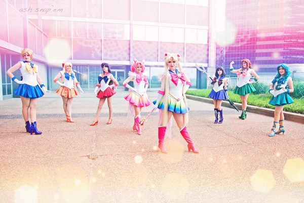 Group shot of 8 cosplayers dressed as Sailor Senshi, with a magical rainbow gradient effect.
