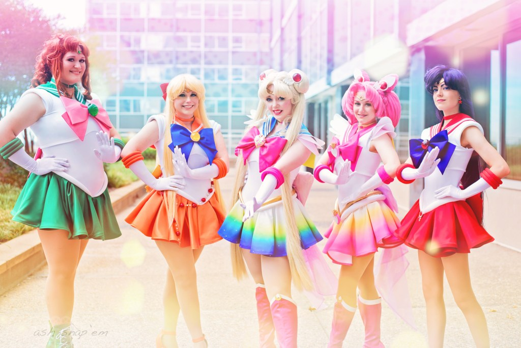 5 cosplayers dressed as Sailor Jupiter, Sailor Venus, Super Sailor Moon, Super Sailor Chibi Moon, and Sailor Mars, posed in a line. A magical rainbow gradient effect adds to their pose.
