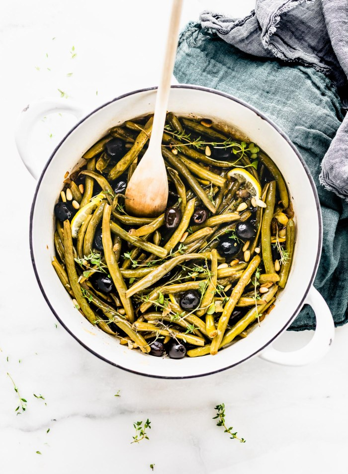 Balsamic Olive-Oil braised green Beans with a quick, easy, and healthy side dish. For this braised green beans recipe, fresh green beans are seasoned with thyme, then braised with balsamic vinegar, olive-oil, onion, black olives, and topped with toasted pine nuts. Paleo, whole 30, and vegan friendly.