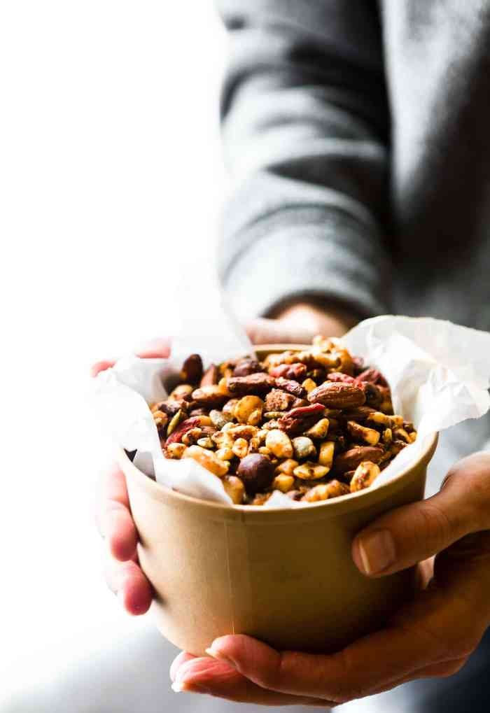 Holding a cup of Thai Curry Spiced Slow Cooker snack mix