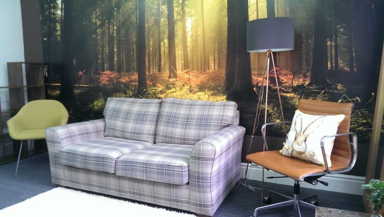 Room with forest wallpaper, blue checked sofa, brown office chair with cushion and green meeting room chair