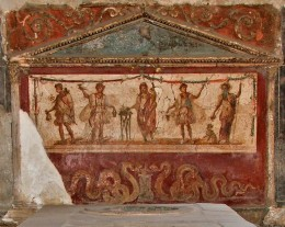 A fresco from the thermopolium of Lucius Vetutius Placidus in the city of Pompeii, depicting the spirit (genius) of the house central, flanked by Lares and Penates with Mercury on far left, Bacchus far right.