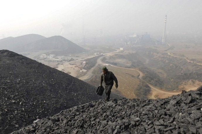 A labourer searches for usable coal at a cinder dump site on the outskirts of Changzhi, Shanxi province October 27, 2009. Spot thermal coal prices in China's top coal shipping port Qinhuangdao continued to rise this week to their highest levels in about 11 months, and the strength is likely to remain as demand grows, traders and analysts said on Tuesday. REUTERS/Stringer (CHINA ENERGY BUSINESS) CHINA OUT. NO COMMERCIAL OR EDITORIAL SALES IN CHINA