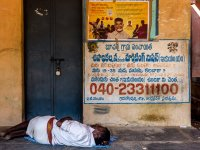 Writing on the wall: an out-of-work Dalit man rests outside the ration store in Bucharla. Ironically, a government helpline number for the jobless is painted on the wall