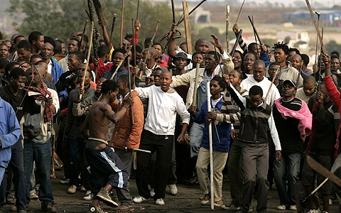Protesters chant slogans during clashes believed to be linked to recent anti-foreigner violence in Reiger Park informal settlement, east of Johannesburg May 20, 2008. South Africa's police and the ruling ANC party intensified efforts on Tuesday to quell deadly violence against foreigners and a government minister said the unrest could damage the key tourism sector. At least 24 people have been killed in over a week of violent attacks on African migrant workers who are accused by many in South Africa's poor townships of stealing jobs and fuelling a wave of violent crime.    REUTERS/Siphiwe Sibeko (SOUTH AFRICA)