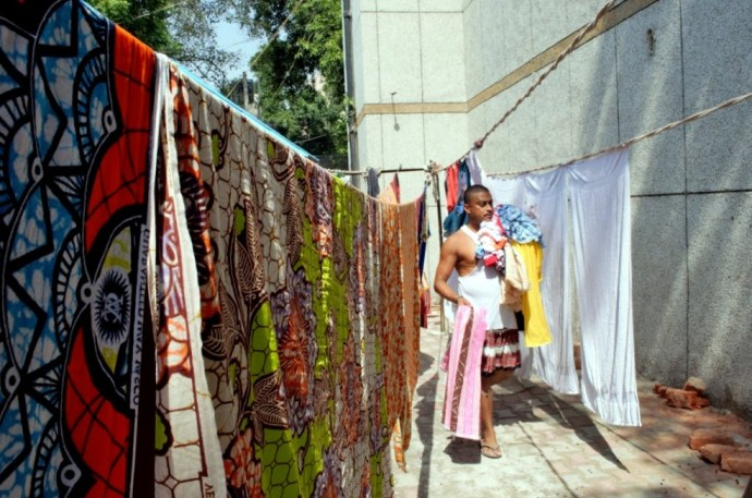 A washerman collecting dried clothes for ironing.