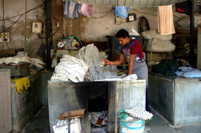 A washerman applies disinfectants to a bundle of clothes at the Devi Prasad Sadan Ghat.