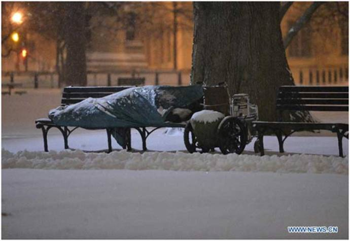"""A homeless sleeps amid a snow storm outside the White House in Washington D.C., capital of the United States…"" [Photo: Xinhua/Zhang Jun]"