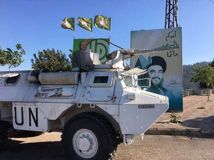UNIFIL vehicle parked in front of Hezollah poster