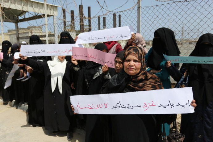 Palestinian women hold banners during a protest calling for an end to intra-Palestinian political divisions that have aggravated the electricity crisis, outside the Gaza Strip's sole functioning generating plant, 23 April. Ashraf Amra APA images