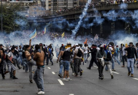 Venezuelan opposition activists clash with the police during a protest against the government of President Nicolas Maduro on April 6, 2017 in Caracas. Violence erupted for a third straight day at protests against the government, escalating tension over moves to keep the leftist leader in power. / AFP PHOTO / JUAN BARRETO