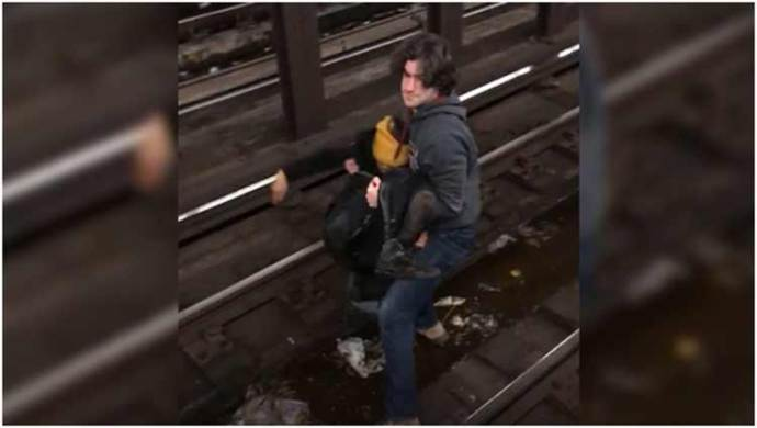 Utility worker jumps onto subway tracks, saves man just before train's arrival