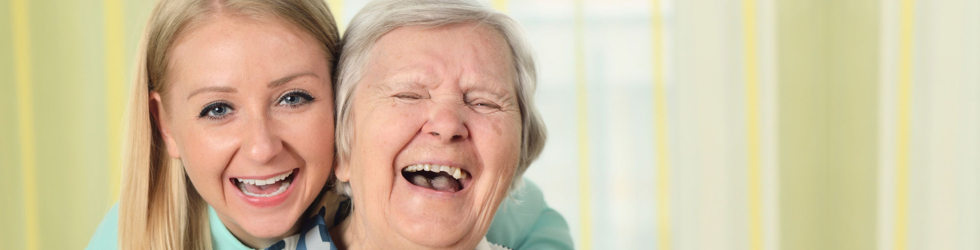 Senior Woman and Assisted Living Aid Laughing