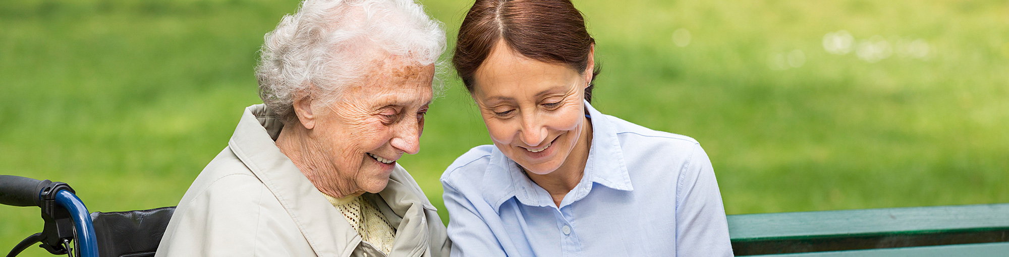 Senior Woman on Bench with Retirement Community Aide