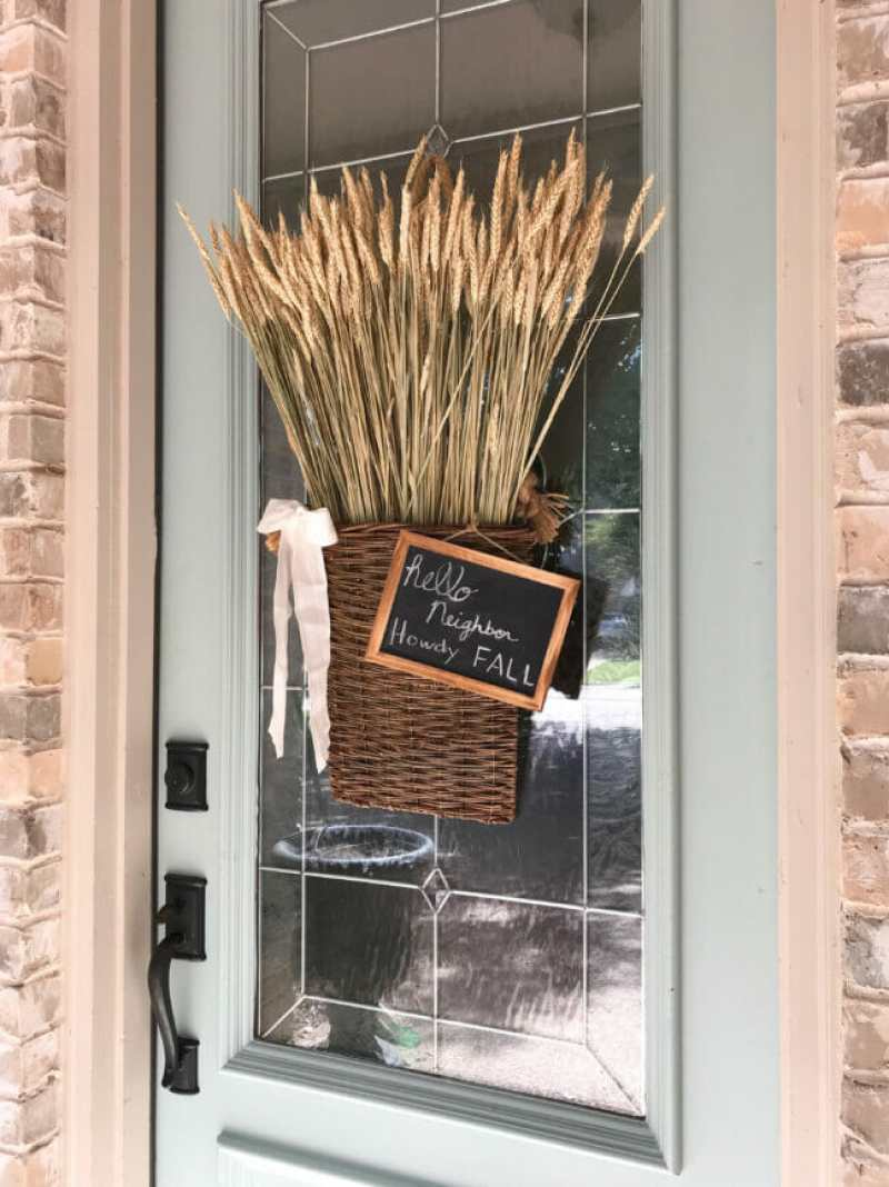front door with hanging willow basket with wheat and chalkboard sign
