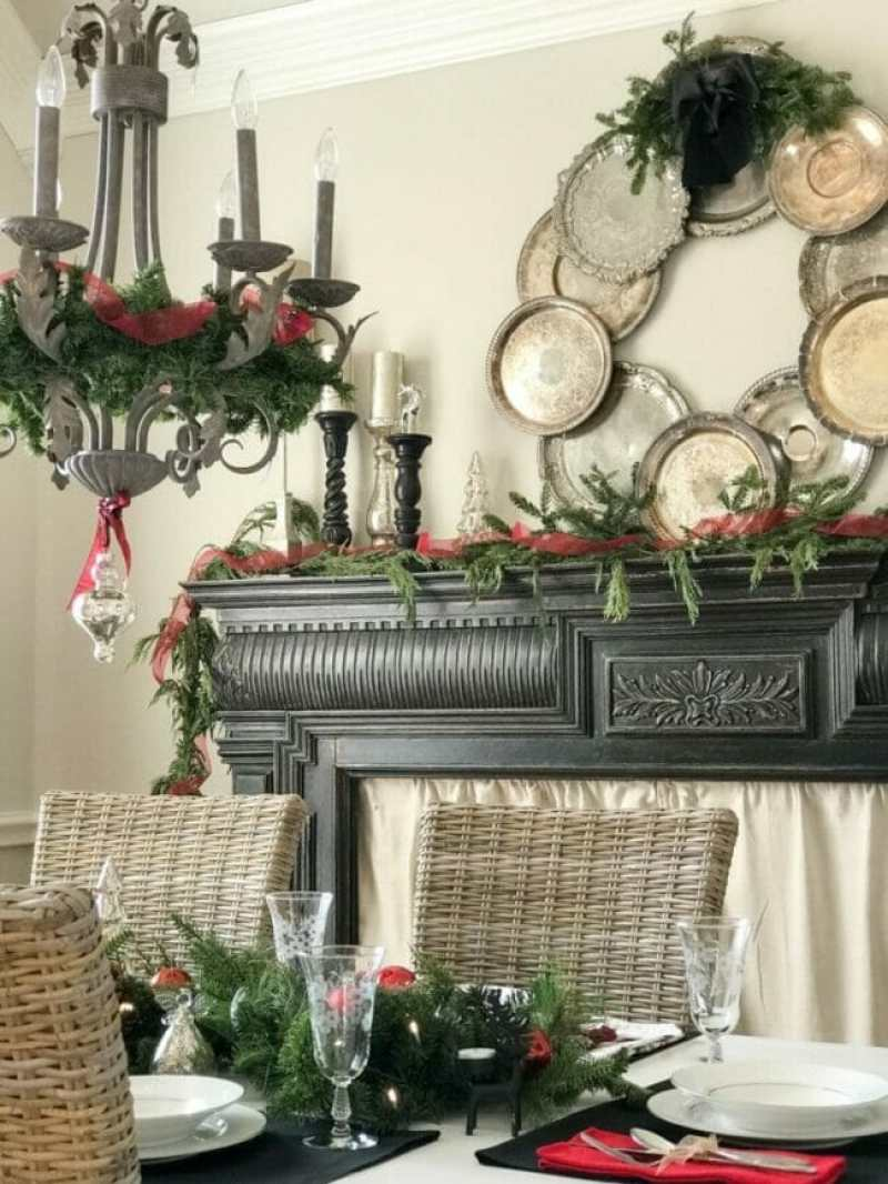 black mantel with silver tray wreath and chandelier with greenery