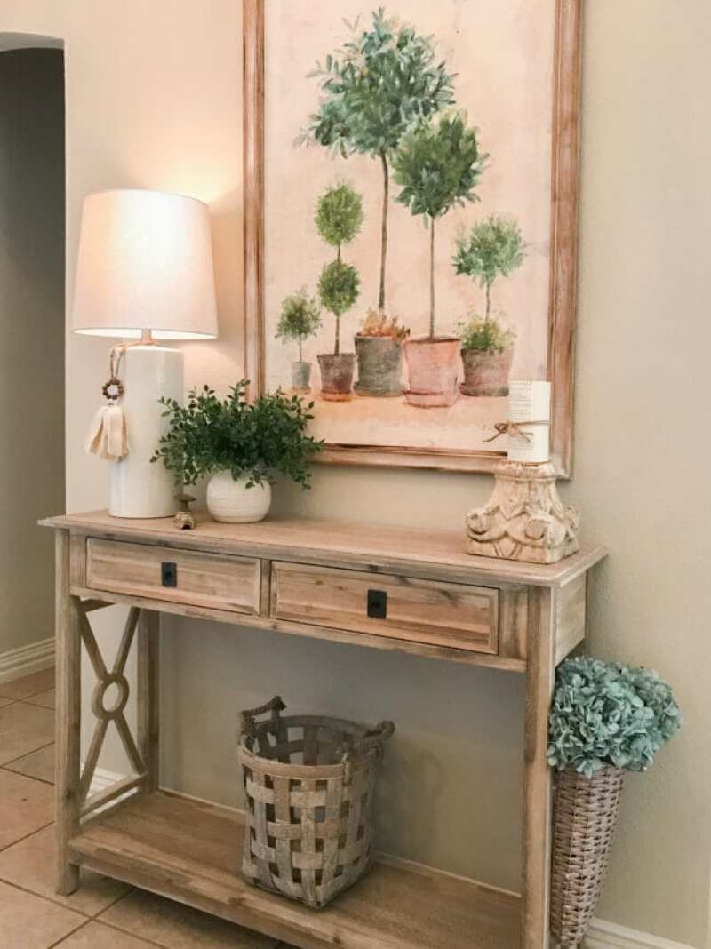 Summer entryway table with lamp, plant and canvas painting of topiaries