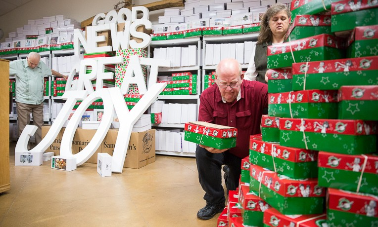 """Pastor Mark Brumbelow and his wife Cherry pray over Operation Christmas Child shoeboxes during a service at Grace Baptist Church in Wild Peach, Texas. Today: US Hurricane Victims """"Pay It Forward"""" to Help Children of Storm-Ravaged Barbuda"""