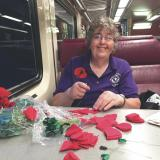 Wearing a poppy supports veterans   Pictured is Ann Fournier making the poppy flowers on the train.