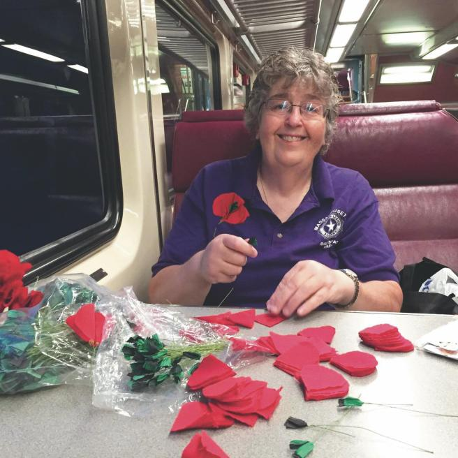 Wearing a poppy supports veterans | Pictured is Ann Fournier making the poppy flowers on the train. | Picture compliments of BrandPoint