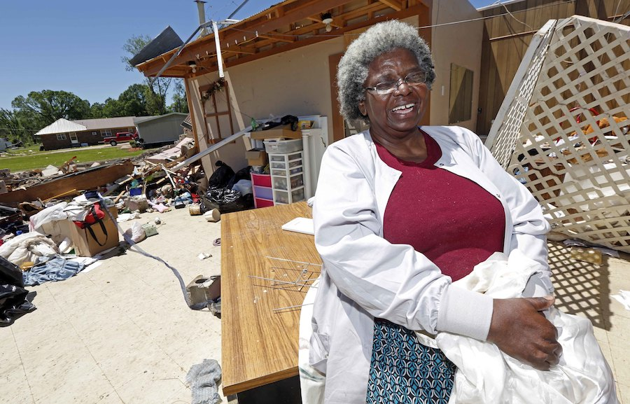 """Mattie Coleman, laughs outside what remains of her combination flower shop, thrift store and laundromat facility Monday, May 1, 2017, in Durant, Miss., as she cleans up from a possible tornado hit on Sunday morning. Coleman, a former teacher and junior high school football coach, takes a philosophical approach to what to the """"remodeling"""" she has before her. (AP Photo/Rogelio V. Solis)"""