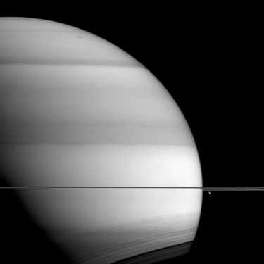 The soft, bright-and-dark bands displayed by Saturn in this view from NASA's Cassini spacecraft are the signature of methane in the planet's atmosphere. This image was taken in wavelengths of light that are absorbed by methane on Saturn. Dark areas are regions where light travels deeper into the atmosphere (passing through more methane) before reflecting and scattering off of clouds and then heading back out of the atmosphere. In such images, the deeper the light goes, the more of it gets absorbed by methane, and the darker that part of Saturn appears. The moon Dione (698 miles or 1,123 kilometers across) hangs below the rings at right. Shadows of the rings are also visible here, cast onto the planet's southern hemisphere, in an inverse view compared to early in Cassini's mission at Saturn (see PIA08168). This view looks toward the unilluminated side of the rings from about 0.3 degrees below the ringplane. The image was taken with the Cassini spacecraft wide-angle camera on Sept. 6, 2015, using a spectral filter which preferentially admits wavelengths of near-infrared light centered at 728 nanometers. The view was acquired at a distance of approximately 819,000 miles (1.32 million kilometers) from Saturn. Image scale is 49 miles (79 kilometers) per pixel. Dione has been brightened by a factor of two to enhance its visibility. The Cassini mission is a cooperative project of NASA, ESA (the European Space Agency) and the Italian Space Agency. The Jet Propulsion Laboratory, a division of the California Institute of Technology in Pasadena, manages the mission for NASA's Science Mission Directorate, Washington. The Cassini orbiter and its two onboard cameras were designed, developed and assembled at JPL. The imaging operations center is based at the Space Science Institute in Boulder, Colorado. For more information about the Cassini-Huygens mission visit http://saturn.jpl.nasa.gov and http://www.nasa.gov/cassini. The Cassini imaging team homepage is at http://ciclop