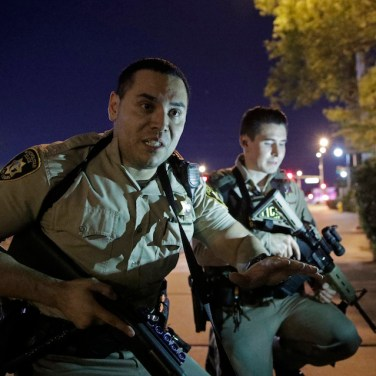 Police officers advise people to take cover near the scene of an Oct. 1, 2017, shooting near the Mandalay Bay resort and casino on the Las Vegas Strip. (AP Photo/John Locher)