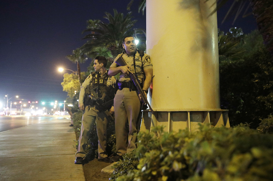 Police officers take cover near the scene of an Oct. 1, 2017, shooting near the Mandalay Bay resort and casino on the Las Vegas Strip. (AP Photo/John Locher)