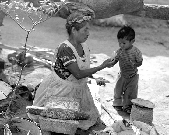 Tortilla maker feeding kid. Mexico (Walt Girdner photo)